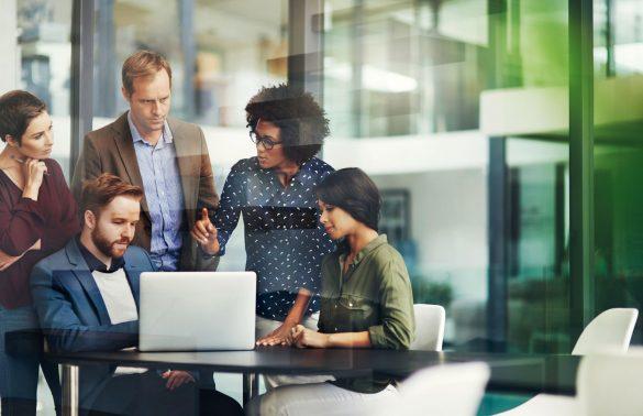 liderar uma equipe: equipe de executivos conversando enquanto olham computador em escritório iluminado e com paredes de vidro