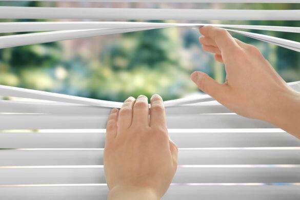 Mulher abre cortina e olha pela janela